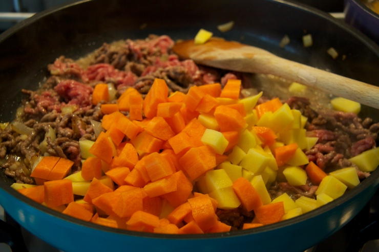MInced beef, potato, carrot, onion and garlic in a frying pan